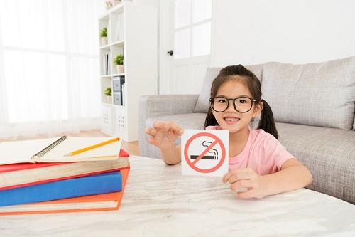 禁煙マークを持つ女の子